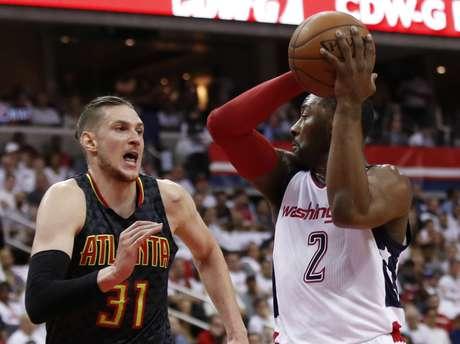 John Wall, de los Wizards de Washington, busca un destinatario para enviarle un pase, frnete a Mike Muscala, de los Hawks de Atlanta, en el primer juego de la serie de playoffs entre ambos equipos, el domingo 16 de abril de 2017