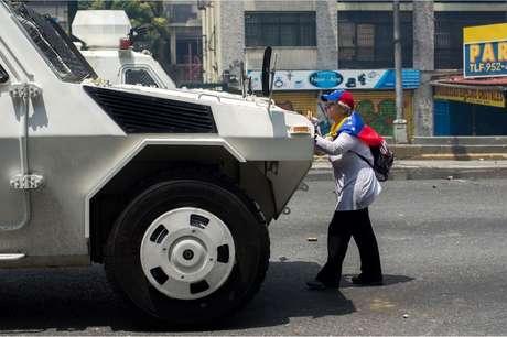 Membros da imprensa e outros manifestantes tentarm tirá-la de frente do tanque sem sucesso