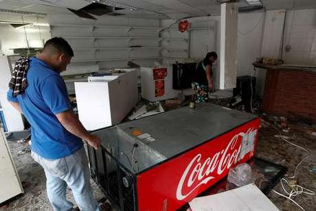 Homem procura por objetos de valor em loja de conveniência saqueada em Caracas, na Venezuela