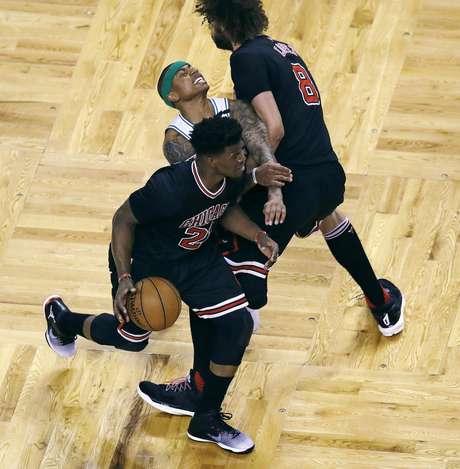 Robin Lopez (8), pivote de los Bulls de Chicago, comete una falta sobre el base Isaiah Thomas, al centro, de los Celtics de Boston que cubría al alero Jimmy Butler (21) durante el primer período en el quinto partido de la serie de playoffs de primera ronda entre ambos equipos, en Boston, el miércoles 26 de abril de 2017