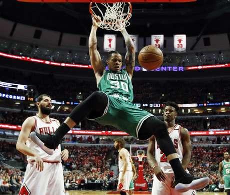Gerald Green, de los Celtics de Boston, clava el balón ante la mirada de los jugadores de los Bulls de Chicago, Nikola Mirotic, a la izquierda, y Jimmy Butler, durante el sexto juego de la serie de playoffs de primera ronda el viernes 28 de abril de 2017 en Chicago
