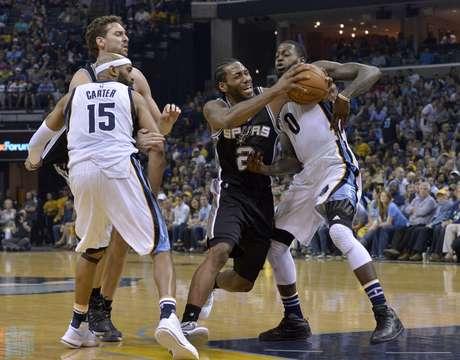El jugador de los Spurs de San Antonio Kawhi Leonard (2) lanza contra el jugador de los Grizzlies de Memphis JaMychal Green (0), mientras el jugador de los Grizzlies Vince Carter (15) y el de los Spurs Pau Gasol, al fondo a la izquierda, se ponen en posición en la segunda mitad de su juego de primera ronda de playoff