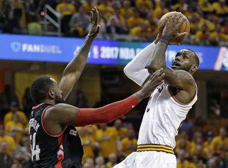LeBron James (derecha) de los Cavaliers de Cleveland dispara al aro sobre Patrick Patterson (54) de los Raptors de Toronto en los playoffs de la NBA, el lunes 1 de mayo de 2017