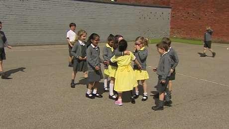 Anu, de 7 anos, aparece pela primeira vez na escola com sua 'nova perna cor-de-rosa' e é recebida por colegas.