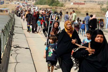 Iraquianos deslocados atravessam o rio Tigre, enquanto as forças iraquianas lutam com militantes islâmicos no oeste de Mossul.