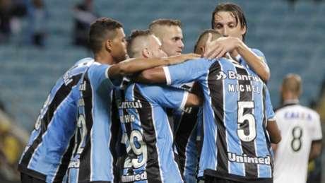 Jogadores gremistas se abraçando após o primeiro gol de Ramiro na Arena (Foto: lItamar Aguiar/Agência Freelancer)