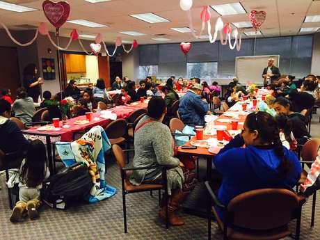 Promotor de Salud, Jonathan Diaz, ofrece educación adicional acerca del manejo del asma durante la celebración para graduados de la clase de asma en el Dia de San Valentín.