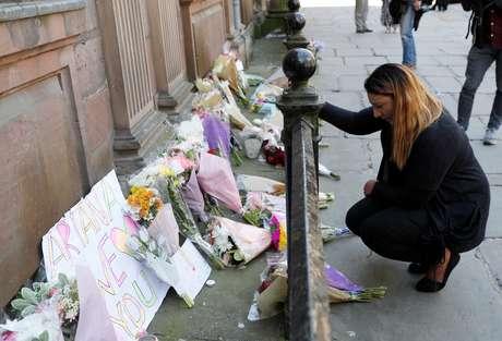 Mulher deposita flores em homenagem às vítimas do atentado após show de Ariana Grande em Manchester.