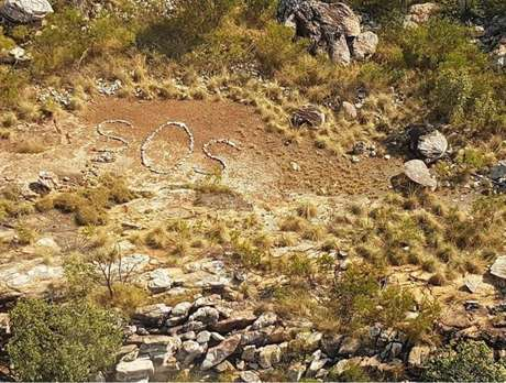 O sinal, feito com pedras, foi avistado por um piloto de helicóptero