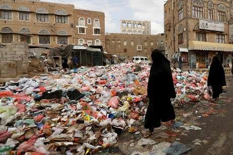 Mulher passa junto a pilha de lixo em Sanaa