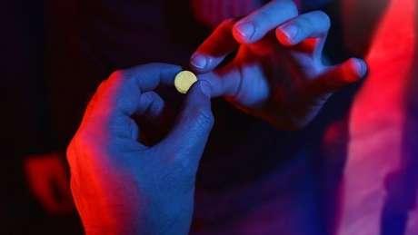 Pessoa pegando um comprimido de ecstasy