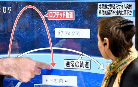 Pedestre vê reportagem sobre lançamento de míssil no Japão