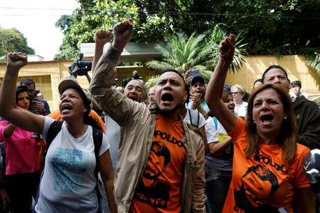 Manifestantes gritam palavras de ordem na entrada da casa do líder da oposição venezuelana Leopoldo López, que foi colocado em prisão domiciliar depois de mais de três anos de prisão