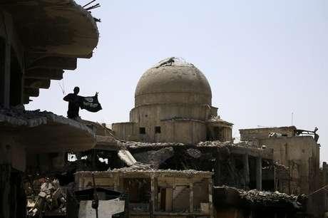 Membro das forças de segurança iraquianas segura a bandeira de militantes do Estado islâmico no topo de um edifício destruído em confrontos na Cidade Velha de Mosul, no Iraque10/07/ 2017. REUTERS/Thaier Al-Sudani