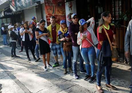 Venezuelanos encaram fila para votar no plebiscito informal sobre o governo de Maduro
