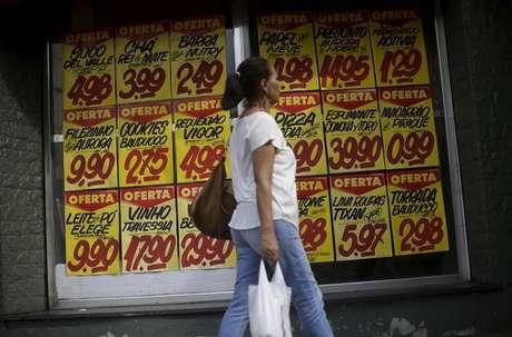 Consumidora passa por cartazes com preços de produtos em mercado no Rio de Janeiro 09/12/2017 REUTERS/Ricardo Moraes