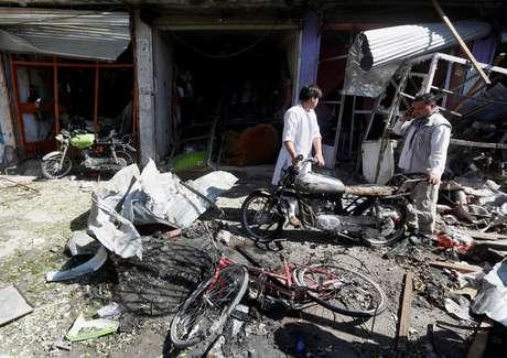Vendedores recuperam pertences em frente  a loja após explosão de carro-bomba em Cabul