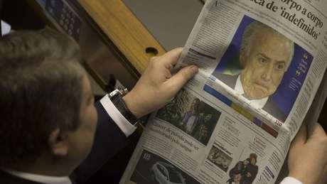 Deputado lê jornal com Temer na manchete