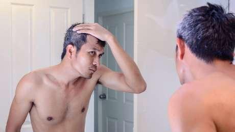 Homem se olha no espelho