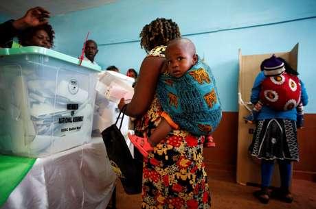 Mulher carregando bebê vota em seção eleitoral na cidade de Gatundu, no Quênia  REUTERS/Baz Ratner