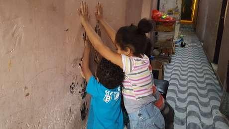 Filhos de Renata brincam no corredor de cortiço onde moram no centro de SP