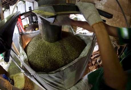 Funcionário preenche saco com grãos de café para exportação, em armazém em Santos 10/12/2015 REUTERS/Paulo Whitaker