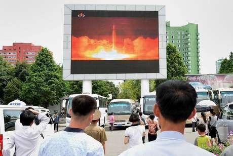 Pessoas assistem à reportagem sobre lançamento de míssil da Coreia do Norte em Pyongyang  Kyodo/via REUTERS
