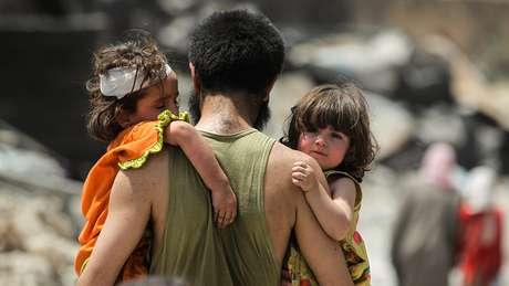 Homem carrega crianças em Mossul