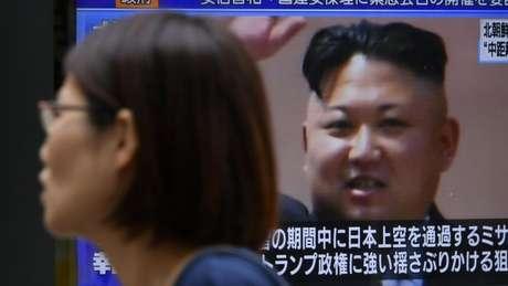 Pedestre em Tóquio passa diante de tela com imagem de Kim Jong-un