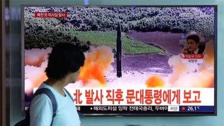 Mulher assiste a reportagem sobre o lançamento de míssil pela Coreia do Norte