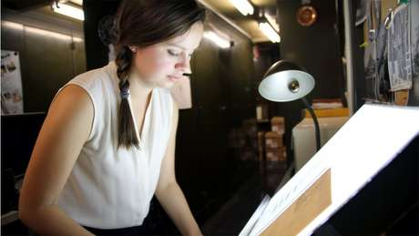 Curadora analisa antiga fotografia em chapa de vidro