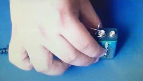 Mão com bateria e clipe