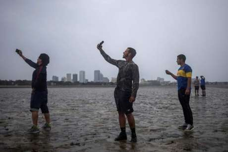 Jovens fazem self na areia da praia