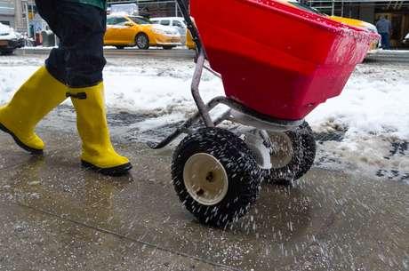Trabalhador espalha sal em rua coberta de neve para agilizar o derretimento do gelo