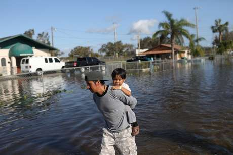 Homem carrega o filho em ruas alagadas de cidade na Flórida