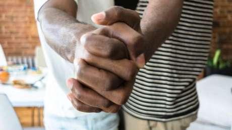 Dois homens negros de mãos dadas