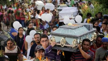 Depois da tragédia na igreja, familiares e amigos da família realizam um enterro coletivo na cidade