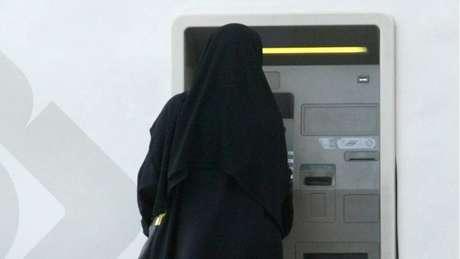 Mulher retira dinheiro em caixa automático na Arábia Saudita