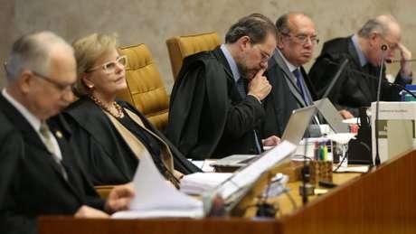 Cinco dos onze ministros do SF sentados em uma bancada no plenário da corte