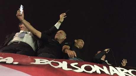 Bolsonaro (à dir., ao microfone) falou à multidão na rua antes de entrar em local de palestra | Foto: Leandro Machado/BBC Brasil