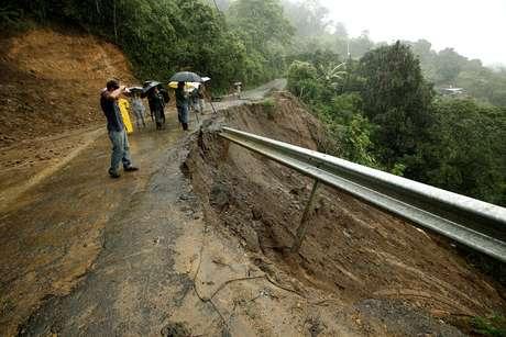 Moradores observam destruição causada pela tempestade em estrada local