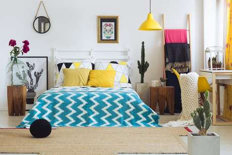 Use composições de almofadas coloridas, quadros e luminárias em tons alegres, como o amarelo, para deixar seu quarto com um ar mais descontraído