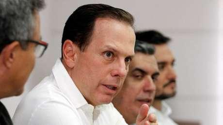 João Doria discursa em uma mesa com empresários