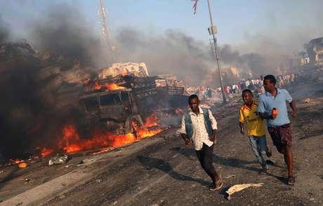 Homens deixam local da explosão na Somália