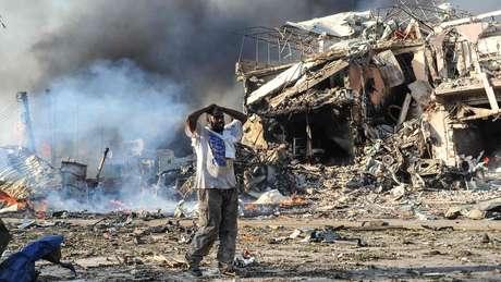 Homem põe as mãos na cabeça ao lado de ruínas e corpos na Somália