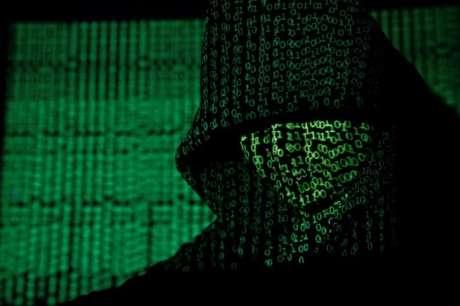 Pessoa encapuzada diante de projeção de códigos cibernéticos 13/05/2017 REUTERS/Kacper Pempel/Illustration