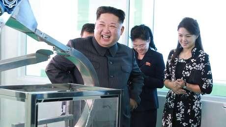 Kim Jong Un rindo e a mulher atrás dele ao lado de outras duas pessoas