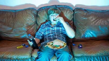 Menino come em frente à TV