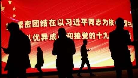 Pessoas em frente a painel com a bandeira chinesa