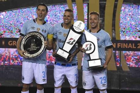 Geromel, Luan e Arthur recebem os troféus de campeão da Libertadores, melhor jogador do torneio e melhor jogador da final, respectivamente